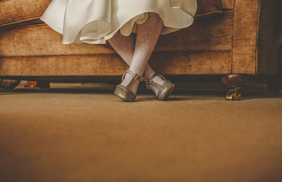 The flower girl sits on the sofa at Orchardleigh House and crosses her legs