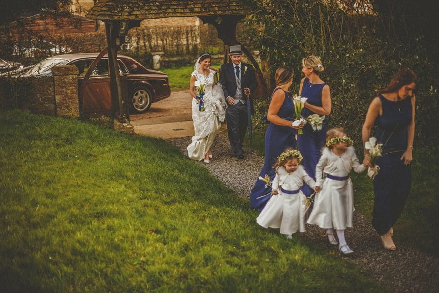 The bride and her family walk towards the Church at Orchardleigh House