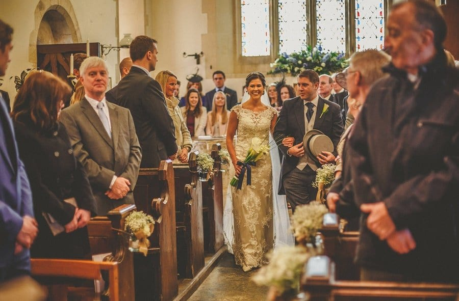 The bride and her brother walk down the aisle of the Church at Orchardleigh House