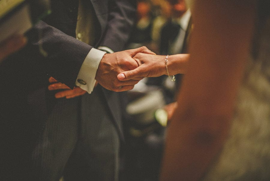 The bride and groom hold hands in the Church