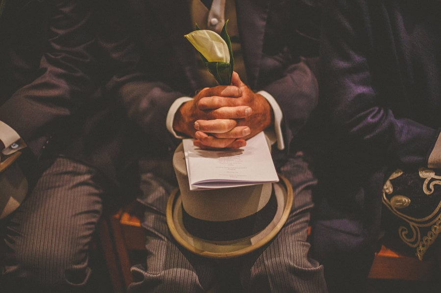 The brides brother holds his hat on his lap and a flower in his hand