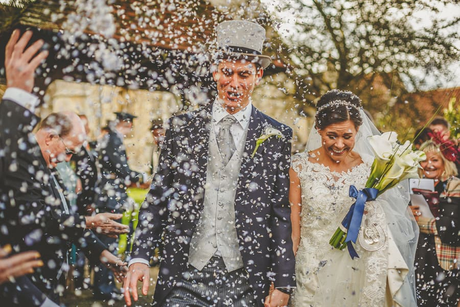 Wedding guests throw confetti over the bride and groom as they walk down the path of the Church