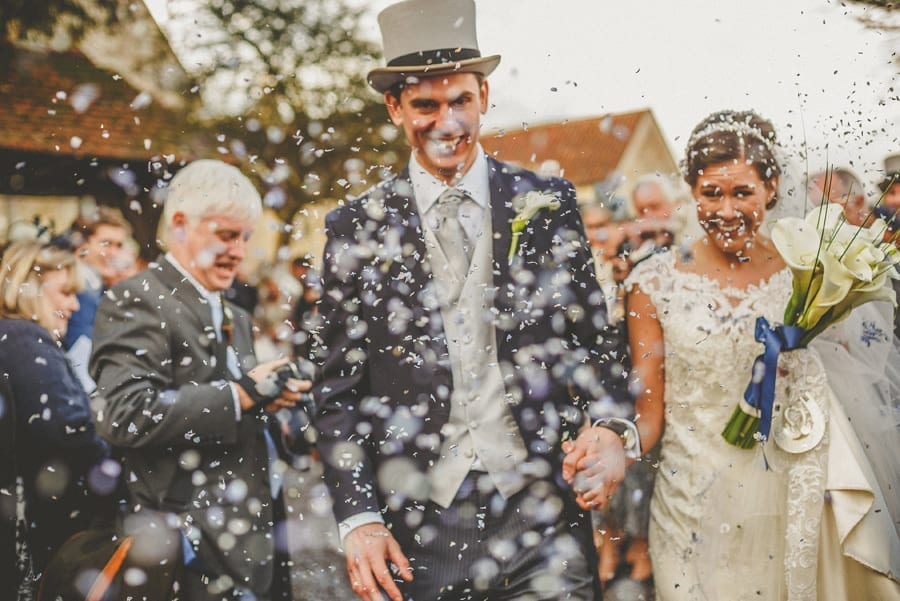 The bride and groom walk away from the Church as the wedding guests throw confetti in the air