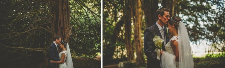 The bride and groom kiss each other under a tree at Orchardleigh House