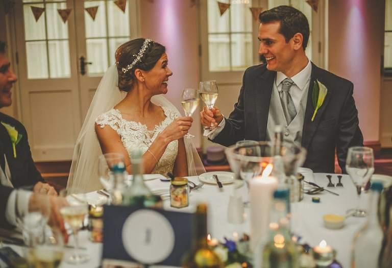 The bride and groom make a toast to one another and smile as they touch glasses
