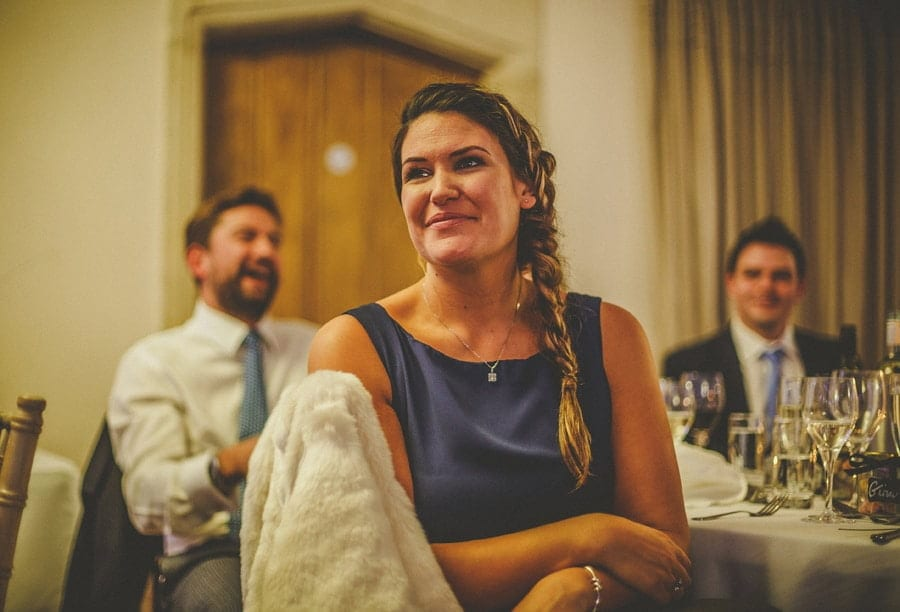 A bridesmaid smiles as she sits at the table and listens to the groom's brothers speeches