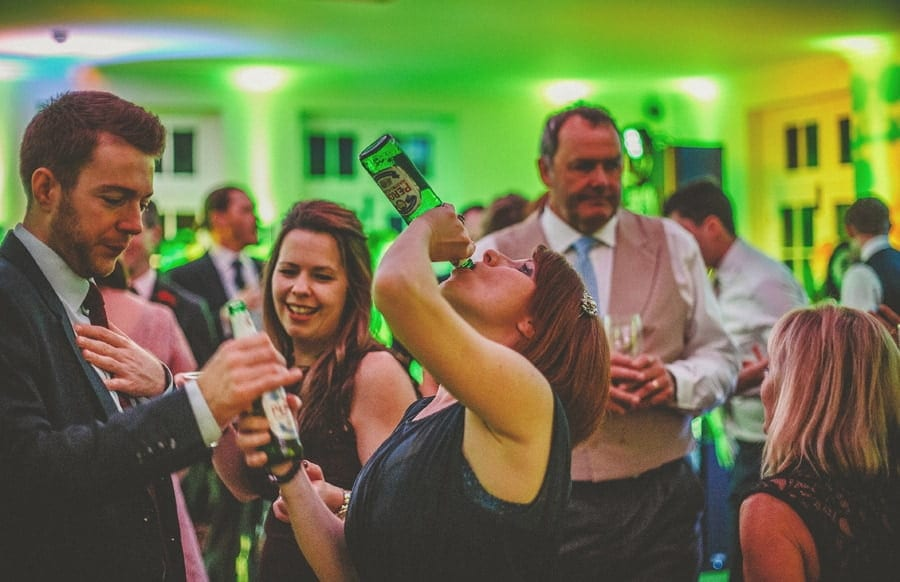 A wedding guest drinks from a bottle on the dancefloor