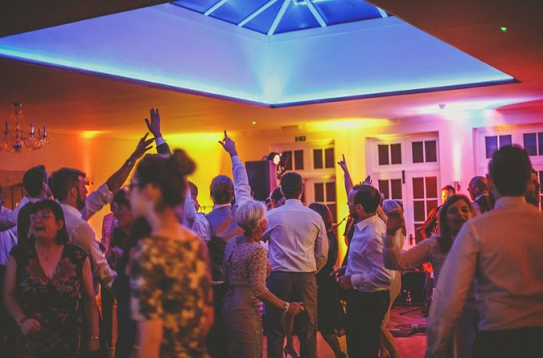 The wedding guests on the dancefloor raise their hands in the air