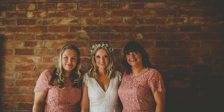 The bride and her bridesmaids pose for a photograph against a large brick wall at Over Barn