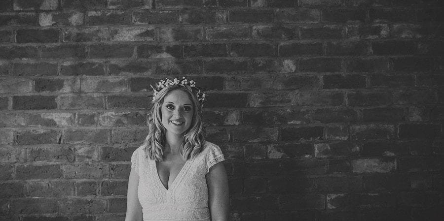 The bride posing for a photograph against a large brick wall
