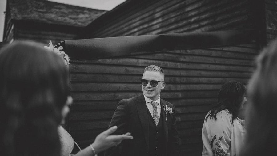 The groom greets friends and family in the courtyard at Over Barn