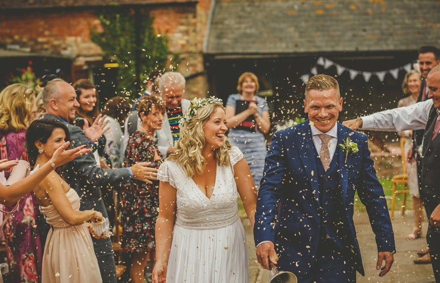 The bride and groom walk down the aisle together and are showered in confetti that is thrown by wedding guests at Over Barn in Gloucestershire
