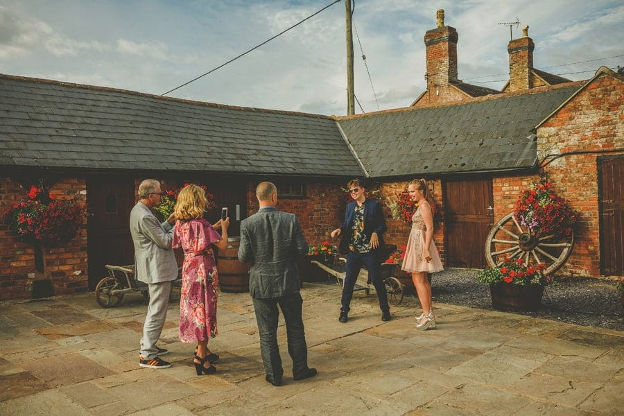 Wedding guests pose for photographs in the courtyard