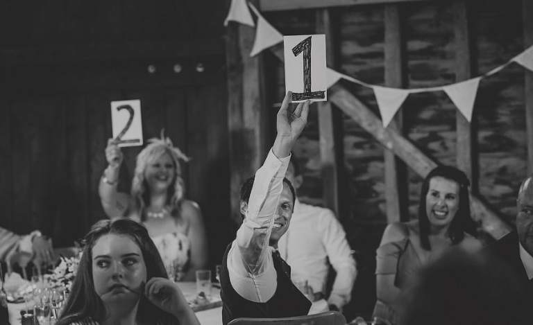 A wedding guest raises a board with the number one on it