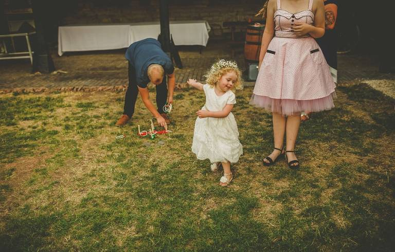 The bride and grooms daughter plays on the grass in the courtyard with her friends and family