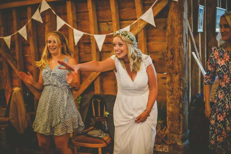 The bride holds her right arm out on the dancefloor at Over Barn