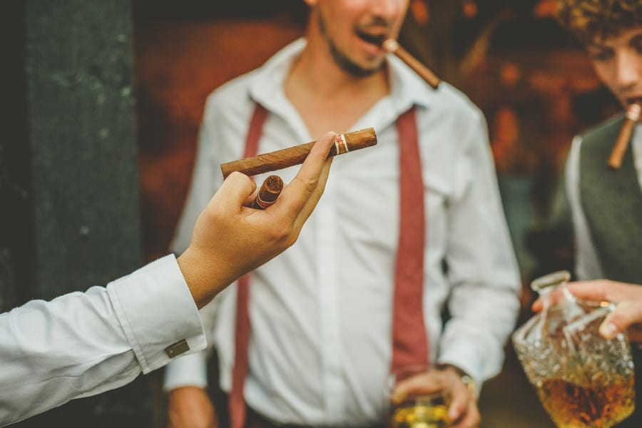 A man offers a cigar to his friend in the courtyard