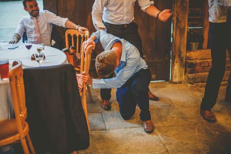 A wedding guest falls onto the floor and attempts to get up in the barn