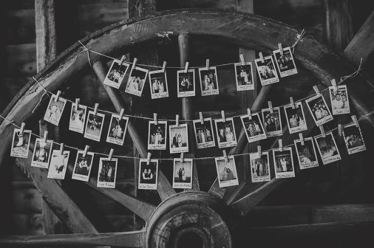 Polaroid photographs hang from string against an old large wooden tractor wheel in the barn