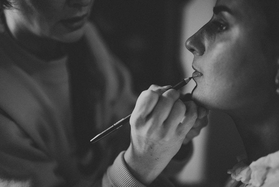 The makeup artist applies lipstick onto the lips of the bride in the cottage in Frome