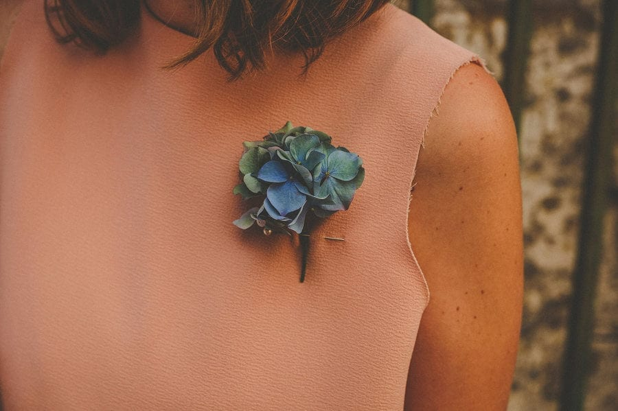 A wedding flower pinned onto the chest of a bridesmaids dress