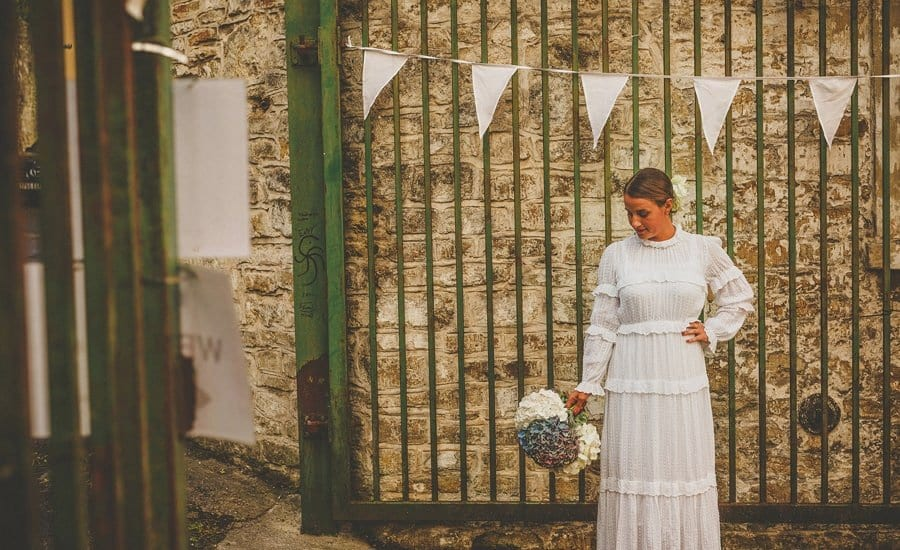 The bride holds her bouquet in her right hand and stands in front of the main gate at Silk Mill Studios in Frome