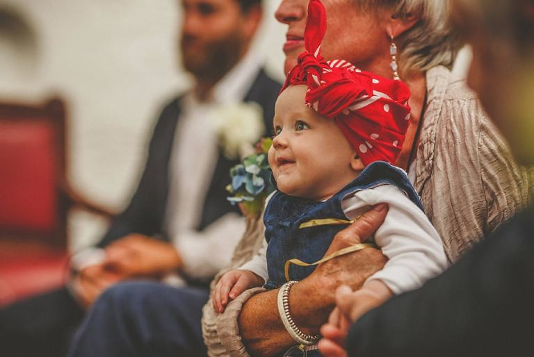 The bride and grooms baby girl smile during the wedding ceremony
