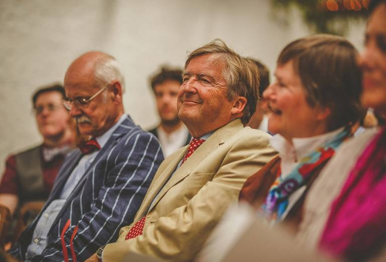 A wedding guest smiles as he sits with friends and family during the wedding ceremony