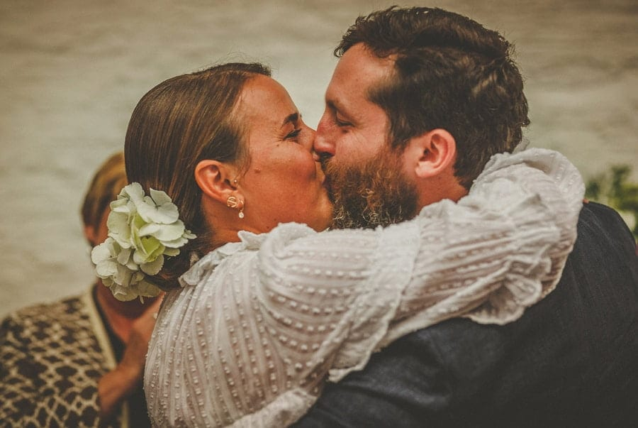 The bride and groom kiss each other