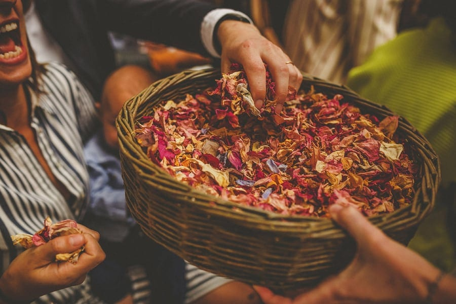 A man picks up confetti from a large wicker bowl