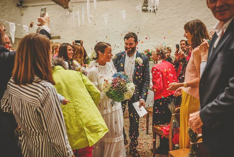 The bride and groom are showered with confetti as they walk down the aisle after the wedding ceremony at Silk Mill studios in Frome