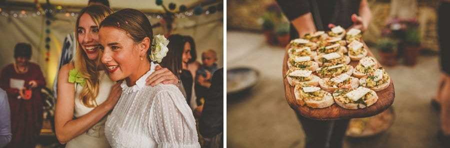 A bridesmaid congratulates the bride and a lady holds out a wooden board of canapes
