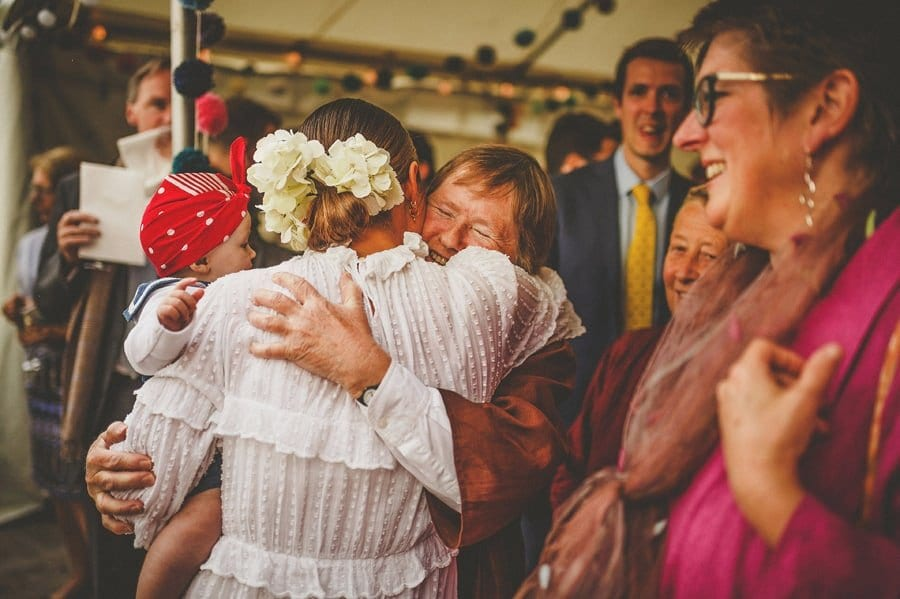 A family member puts her arms around the bride
