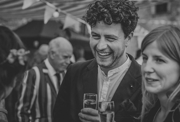 A wedding guest smiles as he chats with friends
