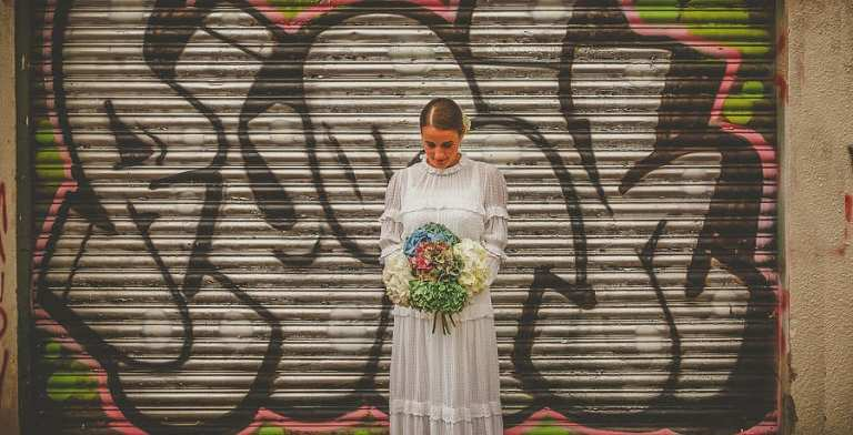 The bride looks down at her bouquet as she stands in front of a large metal shutter
