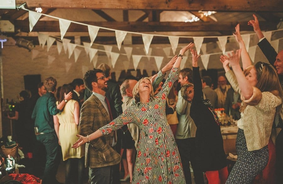 Wedding guests hold their arms up in the air on the dancefloor