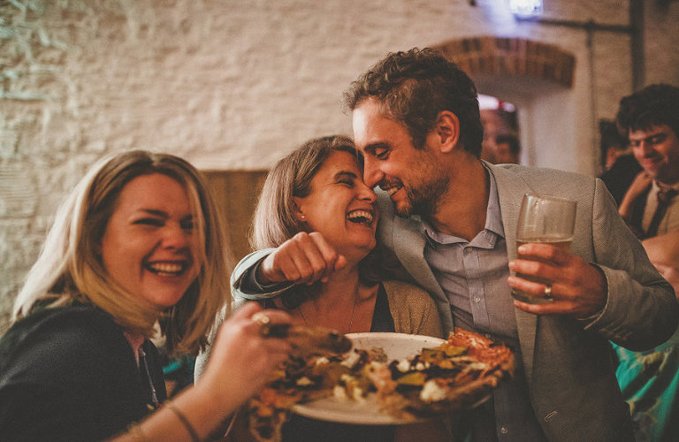 A man puts his arms around his wife as they laugh with one another on the dancefloor