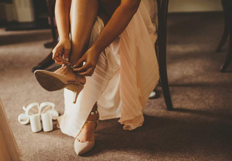 A bridesmaid sits down and puts on her shoes