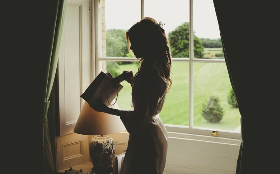 The bride holds a bag full of presents next to the window in the Master bedroom at Stubton Hall