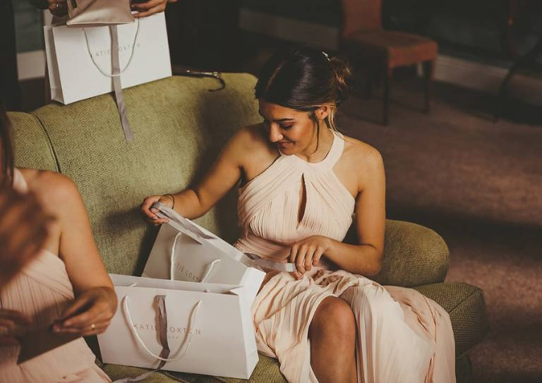 A bridesmaid opens her bag of presents in the Master bedroom