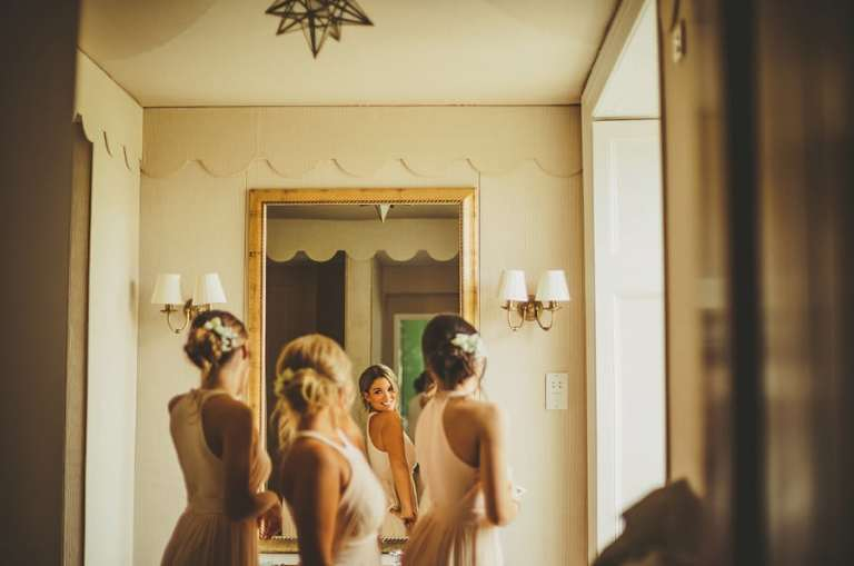 Bridesmaids looking in the mirror and laughing to themselves in the bathroom at Stubton Hall