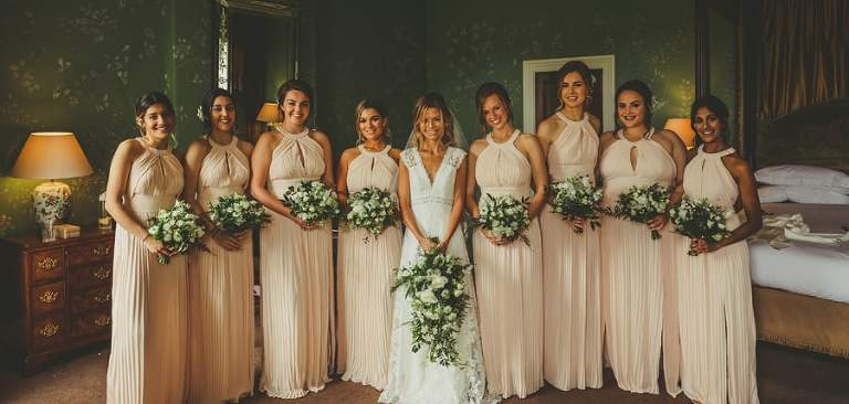 The bride and bridesmaids pose for a photograph in the Master bedroom at Stubton Hall