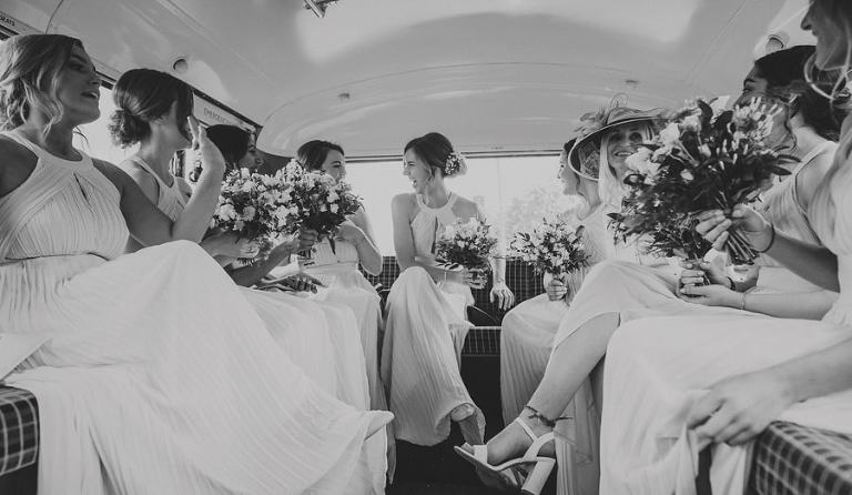 Bridesmaids sit on the back of the wedding bus and share a joke with each other