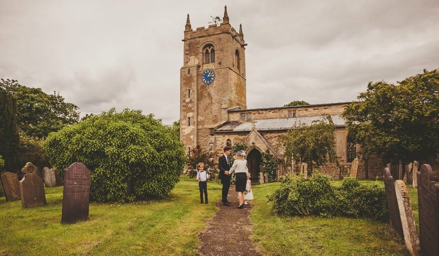 Wedding guests greet each other as they walk towards the Church
