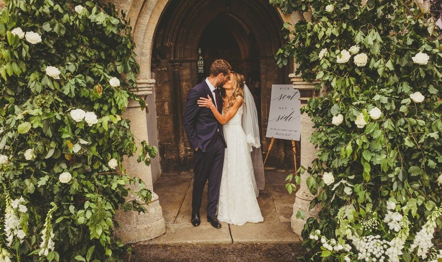 The groom kisses the bride under the arch of the church after the ceremony
