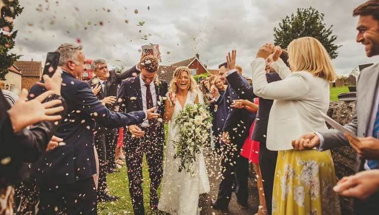 Wedding guests throw confetti over the bride nd groom