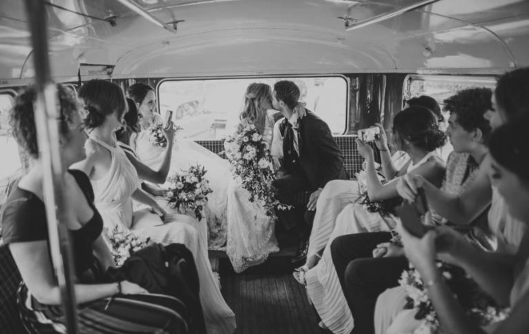 The bride and groom sit on the back of the wedding bus and share a kiss with each other