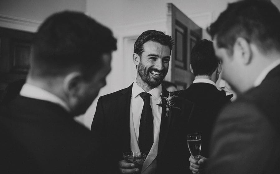 The grooms brother talks amongst the wedding guests