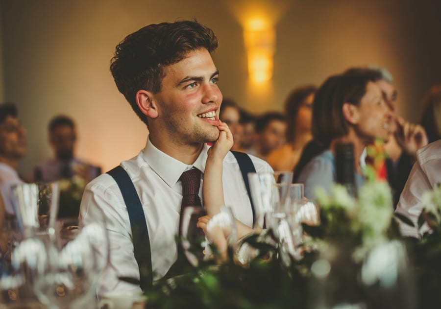 The brides brother smiles during his father's speech