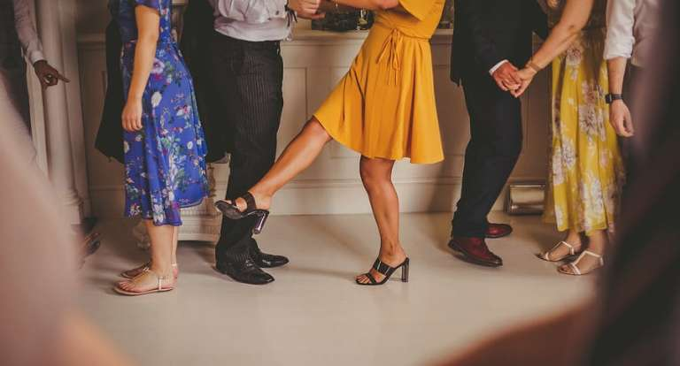 A wedding guest holds out her leg during the ceilidh